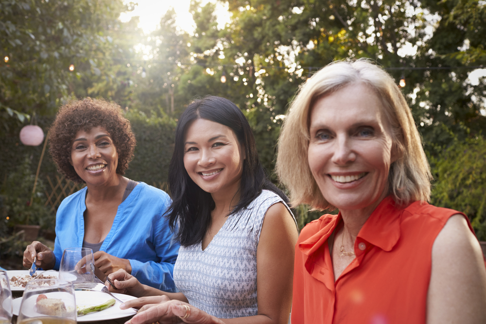 Portrait Of Mature Female Friends Enjoying Outdoor Meal